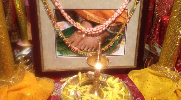 Lit brass lamp in front of photo of Amma's feet