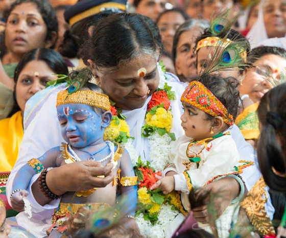 Amma with little children dressed as Krishna sitting on her lap