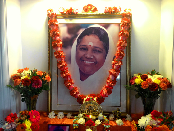 Altar with Amma's picture, garland and flowers