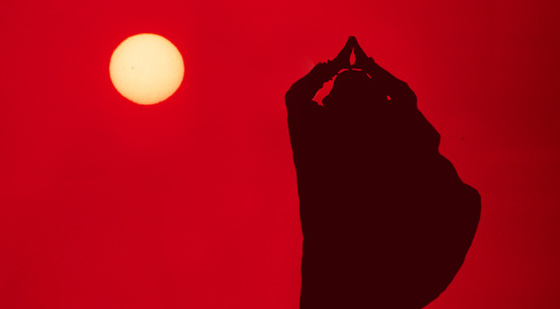 Amma silohette against a red sky with sun
