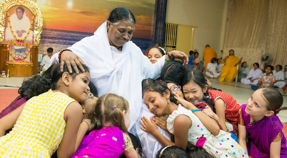 Amma surrounded by little girls hugging her