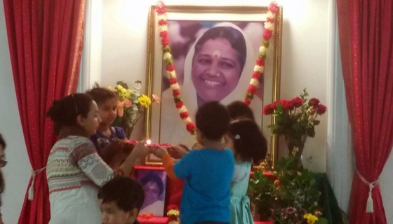 Group of kids doing arati to Amma's picture