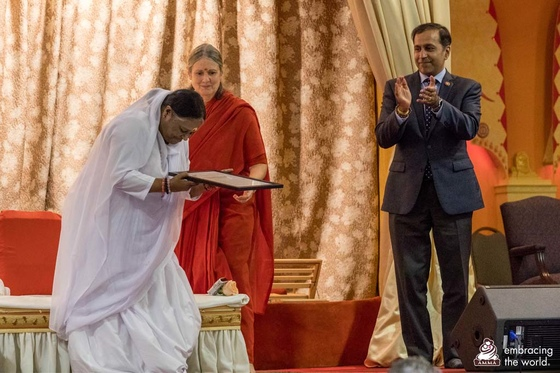 Amma accepting the congressional commendation from Congressman Krishnamoorthi
