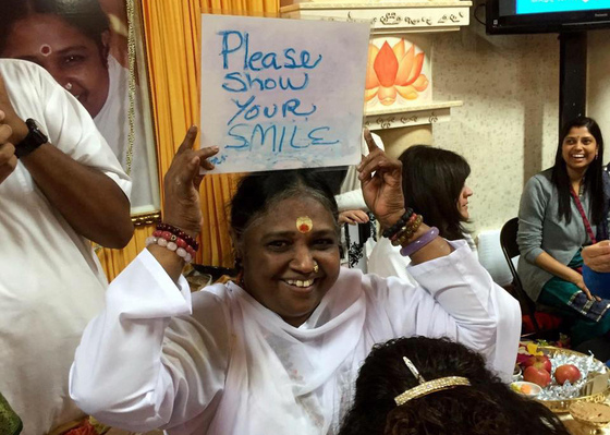 Amma smiling and holding a sign saying 'Please show your smile'