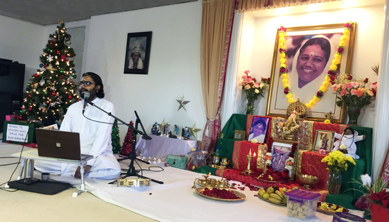 Br. Ramanand speaking at a mic in front of the altar and a Christmas tree