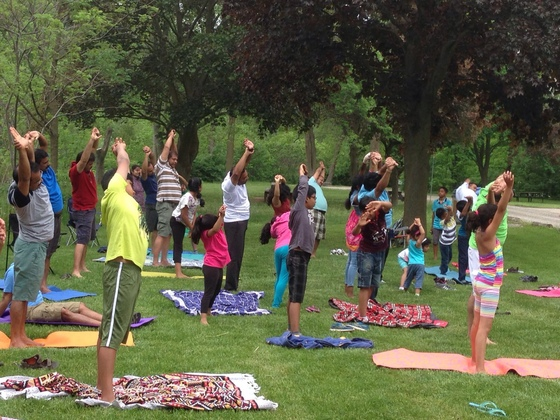 Kids and adults doing yoga together outdoors