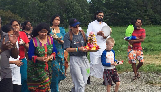 Men, women and children walking in procession in nature