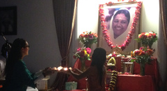 Mother and daughter doing arati together in front of Amma's photo