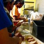 Volunteers buttering bread