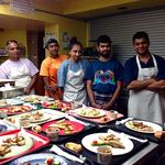 AYUDH members standing beside plated dinners