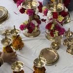 Winding flower garlands around brass lamps