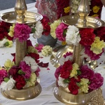 Flower garlands wound around brass lamps