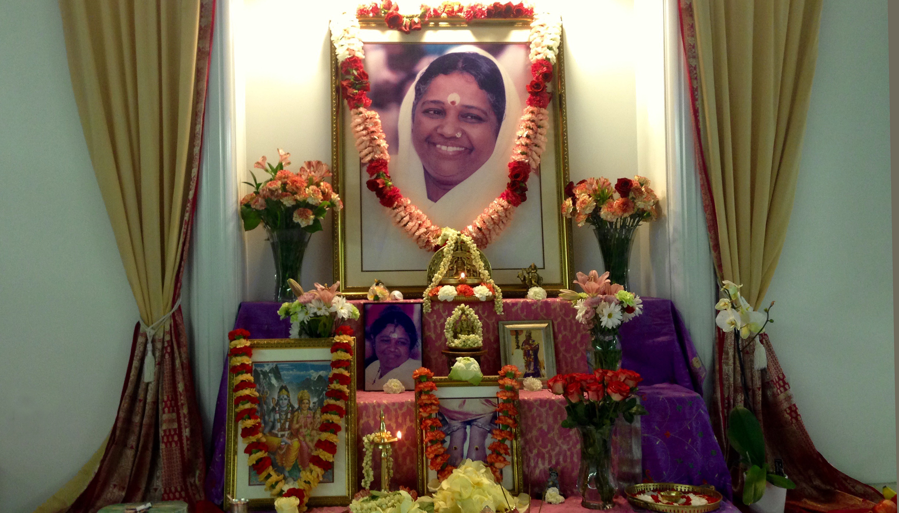 Altar with Amma's photo, garlands and fresh flowers
