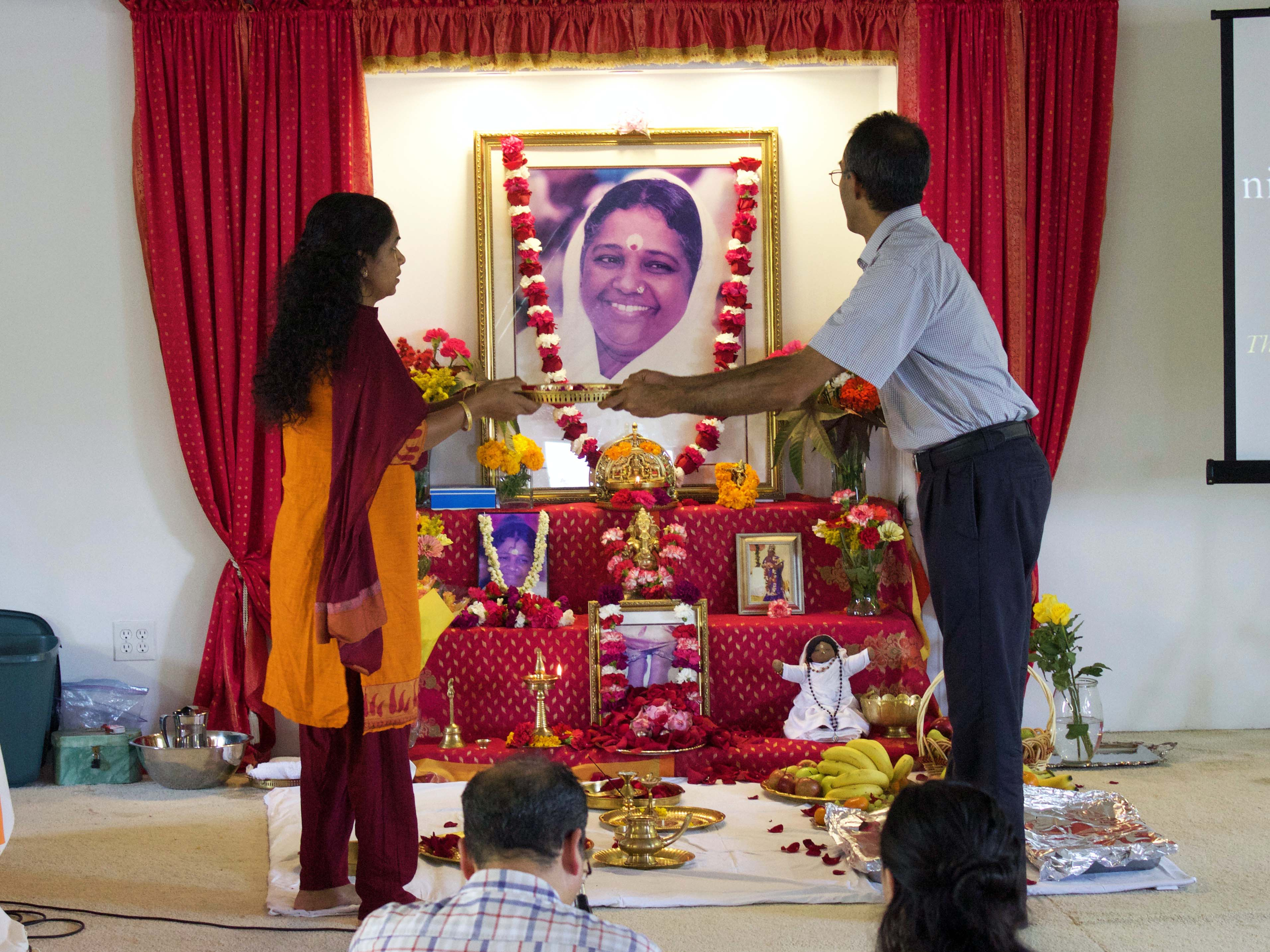 Couple doing arati to Amma