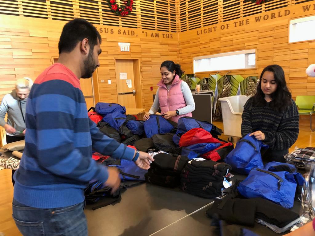 Youth packing backpacks for those in need