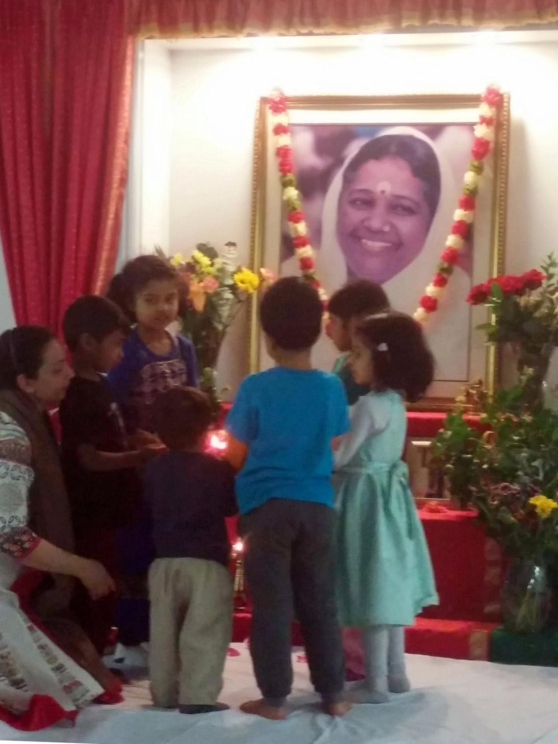 Children doing arati to Amma's photo