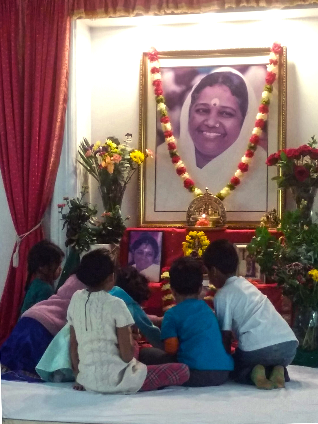 Children offering flower petals before Amma's photo on altar