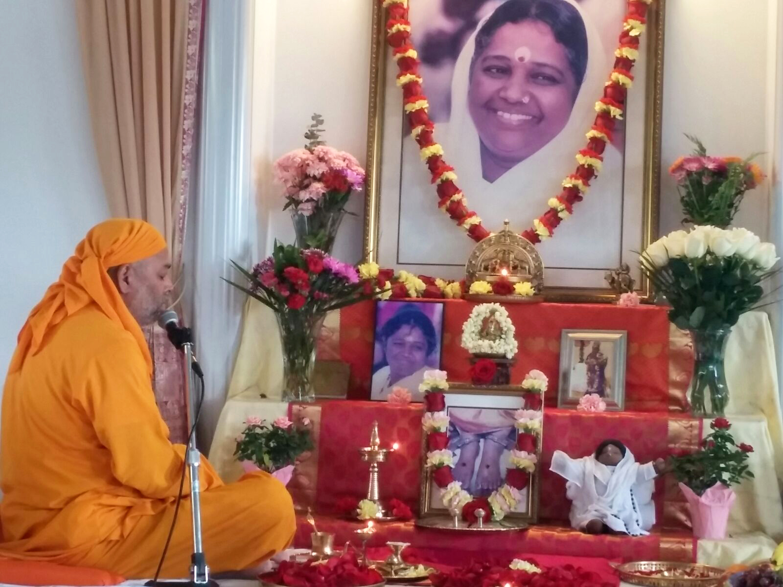Dayamrita Chaitanya sitting by altar