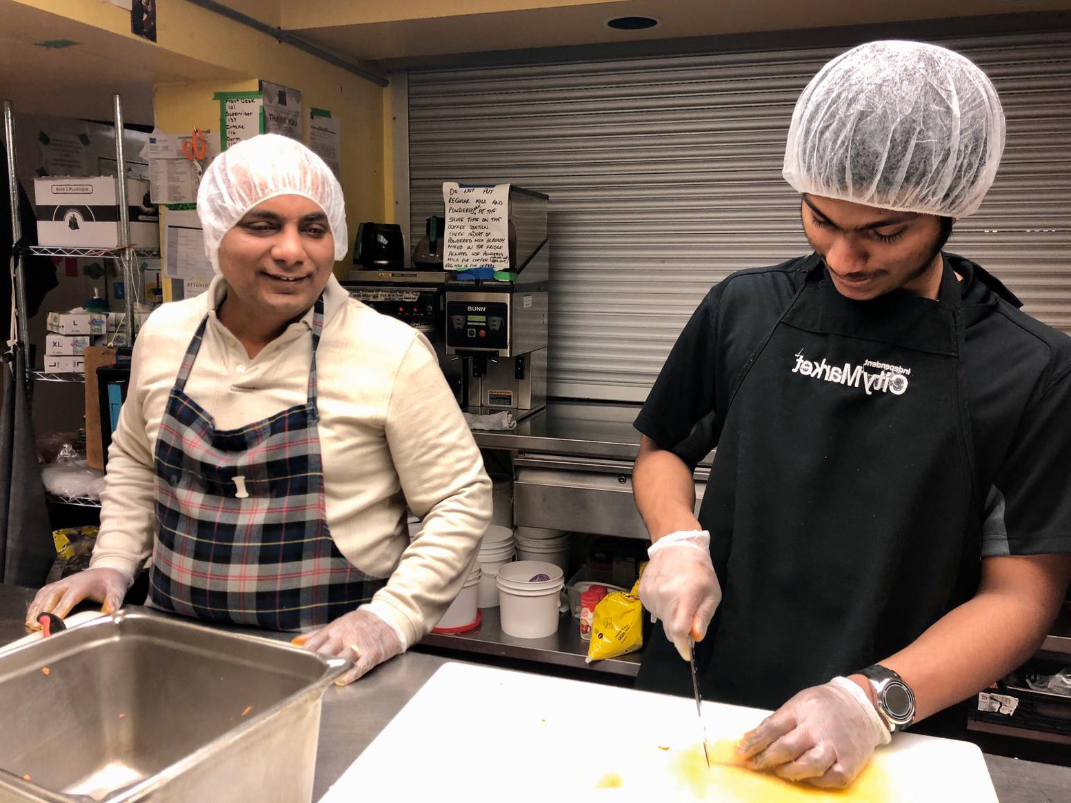 Two AYUDH members and mentor chopping together