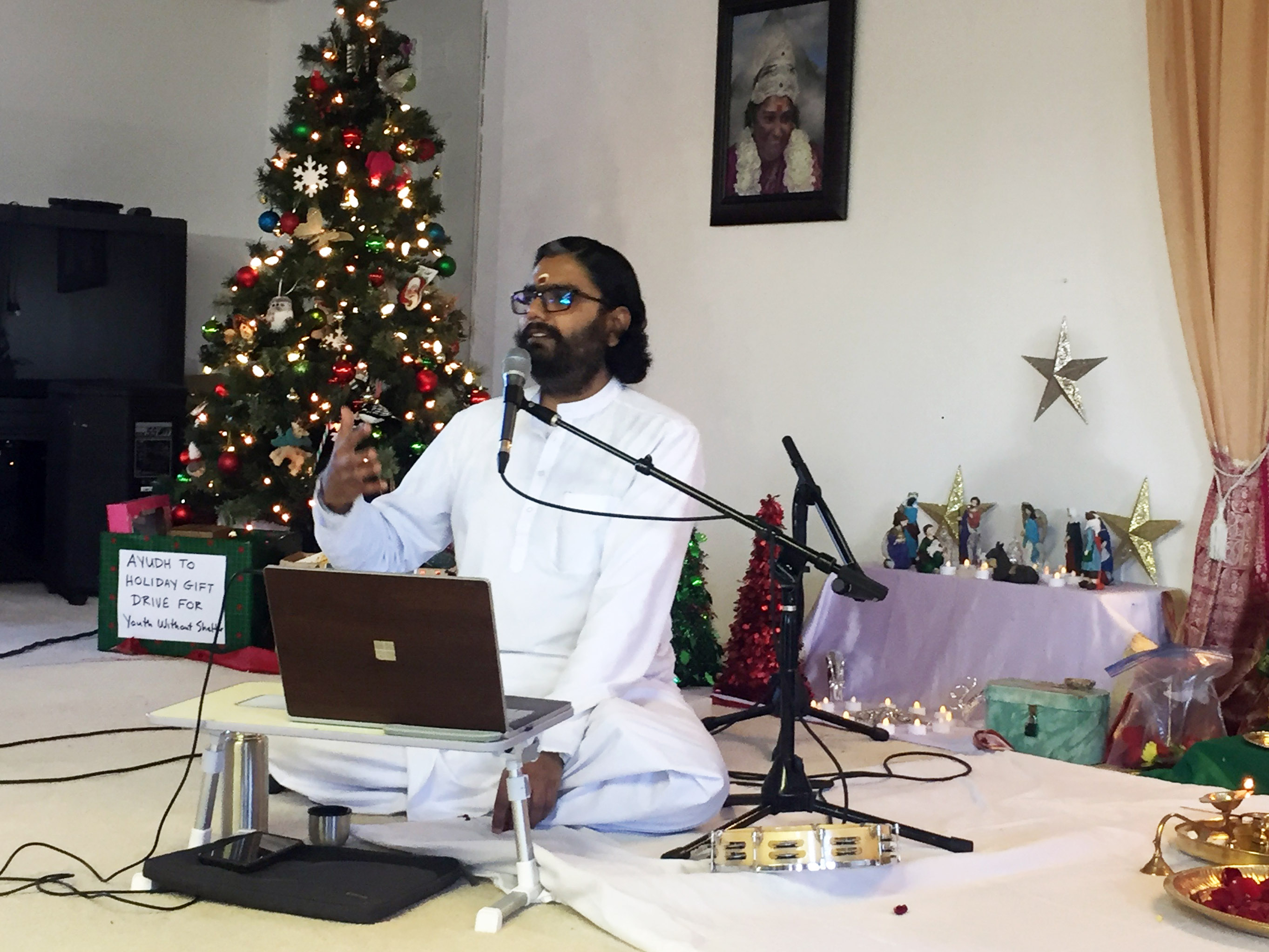 Br Ramanand gesturing and speaking at the mic