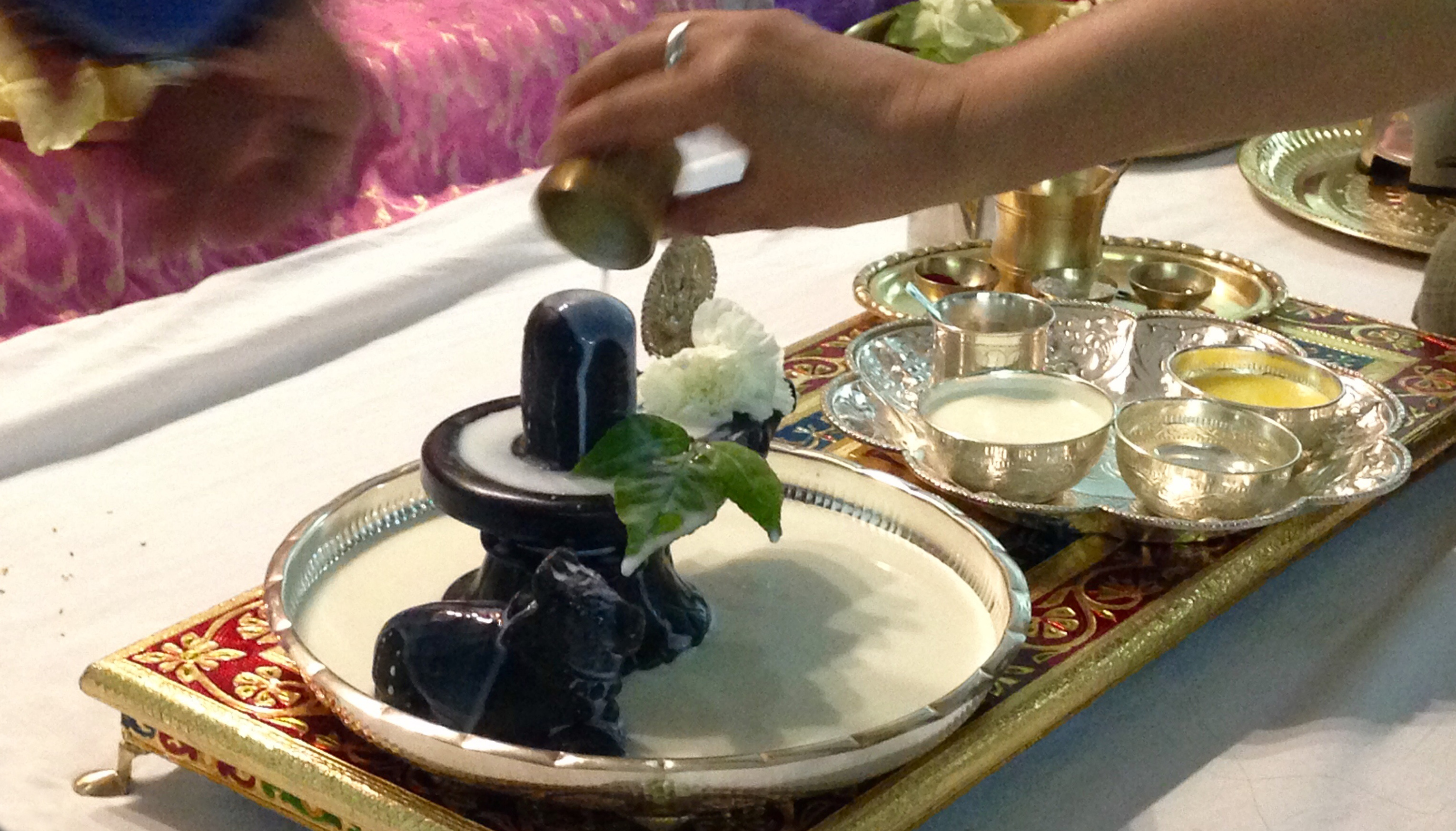 Pouring milk on dark stone Shiva Lingam
